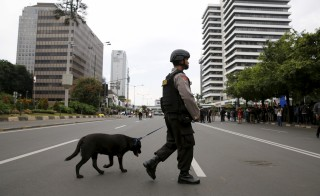 """An Indonesian policeman carries a dog while patrolling at Thamrin business district in Jakarta, January 14, 2016. Militants launched a gun and bomb assault in the centre of the Indonesian capital on Thursday, killing at least six people, police said, in an attack on a country that Islamic State had threatened to put in its """"spotlight"""".  REUTERS/Beawiharta  - RTX22CJW"""