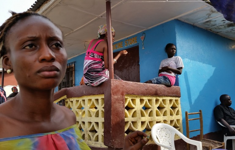 Josephine Karwah, who survived Ebola infection only to be afflicted by other symptoms, stands outside a store in her village of Smell No Taste, Liberia. Photo by Seema Yasmin