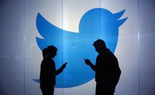 People are seen as silhouettes as they check mobile devices whilst standing against an illuminated wall bearing Twitter Inc.'s logo in this arranged photograph in London, U.K., on Tuesday, Jan. 5, 2016. Twitter Inc. may be preparing to raise its character limit for tweets to the thousands from the current 140, a person with knowledge of the matter said. Photographer: Chris Ratcliffe/Bloomberg via Getty Images