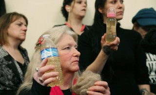 Flint residents Gladyes Williamson, center, holds a bottle of contaminated water, and a clump of her hair during a news conference after attending a House Oversight and Government Reform Committee hearing on the Flint, Michigan, water crisis in February. Photo by Mark Wilson/Getty Images
