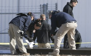 Members of the FBI's evidence response team search the perimeter of Excel Industries on Feb. 26, 2016 in Hesston, Kan. Cedric Ford, an Excel employee, allegedly entered the factory and killed three people and wounded over a dozen others a day before. (Travis Heying/Wichita Eagle/TNS via Getty Images)