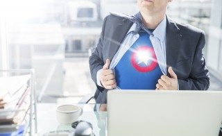 Businessman opening shirt to reveal superhero costume