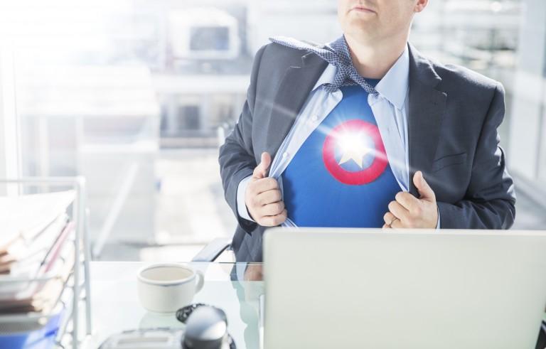 Businessman opening shirt to reveal superhero costume
