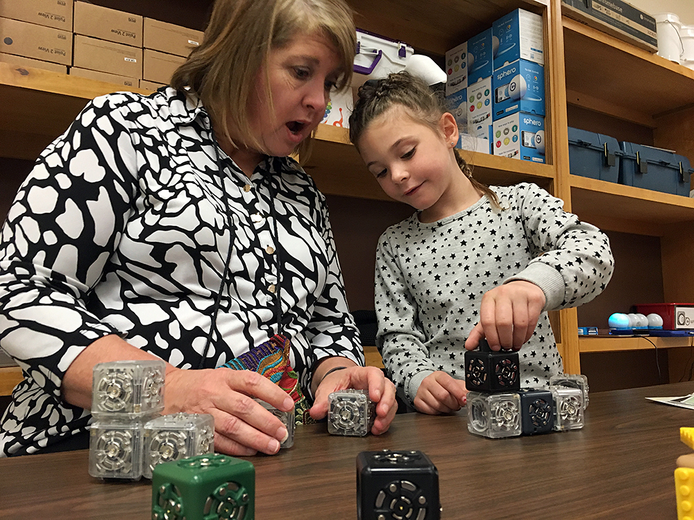 """Principal Janalyn Taylor exclaims as Layla Lee, 5, shows her how she's made a moving robot out of """"cubelets"""" in the maker space at Nance Elementary in Clinton, Oklahoma. Photo: Lillian Mongeau"""