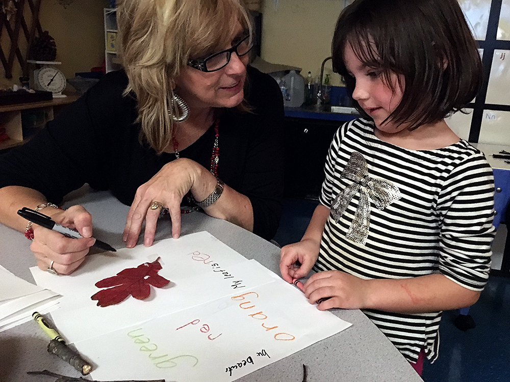 Teacher Jana Dunlap works with Grace Marder, 4, to come up with adjectives to describe a leaf the child found on a nature walk outside the Early Childhood Center in Muskogee, Oklahoma. Photo: Lillian Mongeau