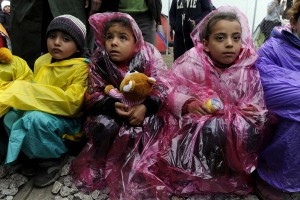 Children are covered with plastic raincoats as stranded refugees wait for the border crossing to reopen near the Greek village of Idomeni, February 28, 2016. Alexandros Avramidis/Reuters