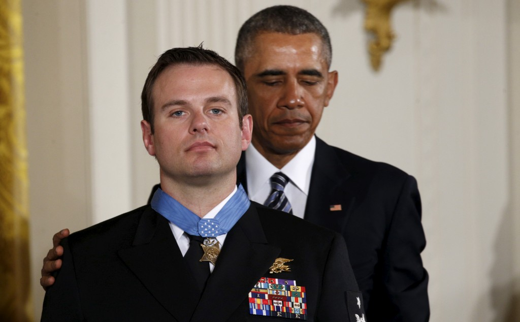 President Barack Obama (R) puts his hand on the shoulder of U.S. Navy Senior Chief Special Warfare Operator Edward Byers after awarding him the Medal of Honor during a ceremony at the White House. Byers was honored for his courageous actions while serving as part of a team that rescued an American civilian being held hostage in Afghanistan on December 8-9, 2012. Photo by Kevin Lamarque/Reuters