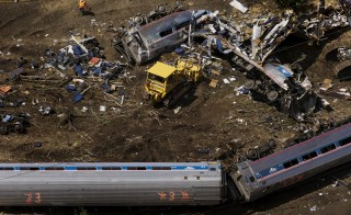 Emergency workers and Amtrak personnel inspect a derailed Amtrak train in Philadelphia, Pennsylvania May 13, 2015. The commuter rail route where an Amtrak train left the track on Tuesday was not governed by an advanced safety technology meant to prevent high-speed derailments, officials familiar with the investigation said on Wednesday. REUTERS/Lucas Jackson  - RTX1CUNR