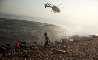 "A Frontex helicopter patrols over a Syrian child that has just arrived at a beach at the Greek island of Lesbos August 10, 2015. Thousands of refugees and migrants are stranded on Greek islands -- in some cases for over two weeks -- waiting for temporary documents before continuing their travel to northern Europe. The United Nations refugee agency (UNHCR) called on Greece to take control of the ""total chaos"" on Mediterranean islands, where thousands of migrants have landed. About 124,000 have arrived this year by sea, many via Turkey, according to Vincent Cochetel, UNHCR director for Europe. REUTERS/Antonis Pasvantis      TPX IMAGES OF THE DAY      - RTX1NQNO"