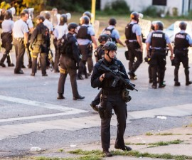 Police line up to block the street as protesters gathered after a shooting incident in St. Louis, Missouri August 19, 2015. Police fatally shot a black man they say pointed a gun at them, drawing angry crowds and recalling the racial tensions sparked by the killing of an unarmed African-American teen in nearby Ferguson, Missouri, just over a year ago.  REUTERS/Kenny Bahr - RTX1OVB4