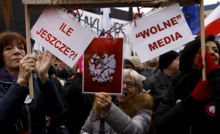 """People gather during an anti-government demonstration for free media in front of the Polish television building in Warsaw on Jan. 9. The placards read """"How many more?"""" (left) and """"Free Media"""". Photo by Kacper Pempel/Reuters"""