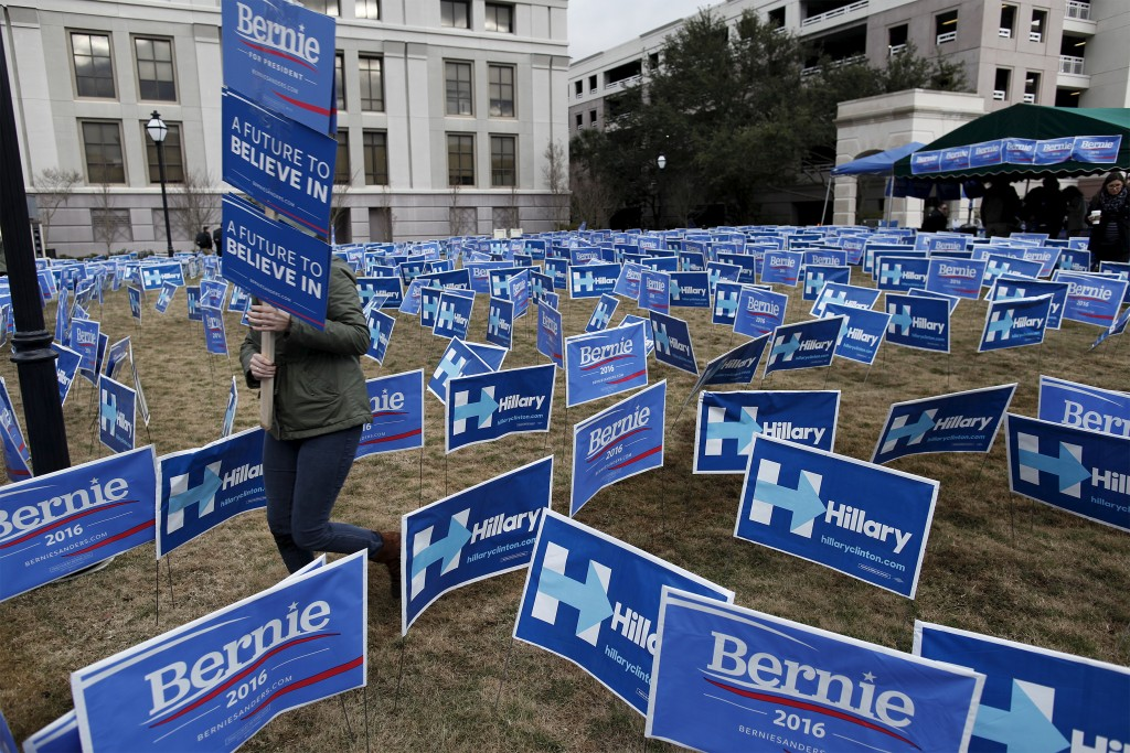 A Bernie Sanders supporter carries a sign through a maze of political sign for Sanders and opponent Hillary Clinton in Charleston, South Carolina, January 17, 2016. Photo by Randall Hill/Reuters.