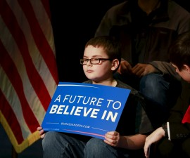 """A child holds a sign that reads """"A Future to Believe In"""" before U.S. Democratic presidential candidate and U.S. Senator Bernie Sanders addressed students and community members during a campaign meeting with students at Concord High School in Concord, New Hampshire January 22, 2016. Photo by Katherine Taylor/Reuters."""