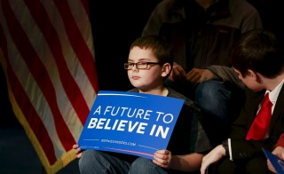 "A child holds a sign that reads ""A Future to Believe In"" before U.S. Democratic presidential candidate and U.S. Senator Bernie Sanders addressed students and community members during a campaign meeting with students at Concord High School in Concord, New Hampshire January 22, 2016. Photo by Katherine Taylor/Reuters."
