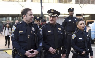 San Francisco Police Chief Greg Suhr (C) walks through Super Bowl City in San Francisco, California, days before the sports event this weekend. The Justice Department said it will review the city's police procedures, two months after the fatal police shooting of 26-year-old Mario Woods, a black man. Photo by Noah Berger/Reuters