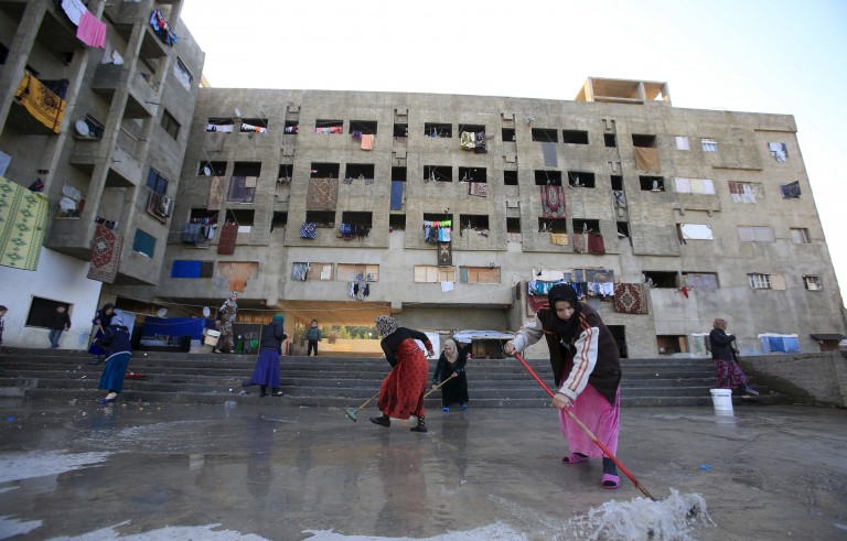 Women clean the floor of a compound housing Syrian refugees in Sidon, southern Lebanon February 3, 2016. Lebanon has weathered five years of Middle Eastern turmoil remarkably well but its stability should not be taken for granted and it needs long-term financial help to cope with a huge number of Syrian refugees, a senior U.N. official said. To match MIDEAST-CRISIS/LEBANON REUTERS/Ali Hashisho   - RTX25BBK