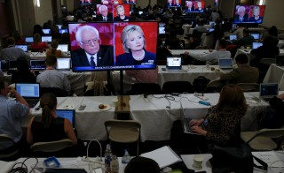 Democratic presidential candidates Hillary Clinton (R) and Bernie Sanders appear on televisions in the media room of the fifth Democratic debate sponsored by MSNBC in Durham, New Hampshire. Photo by Adrees Latif/Reuters