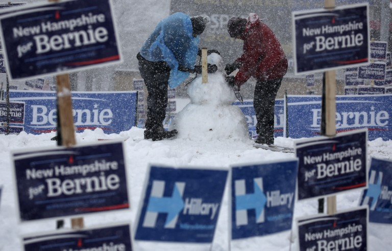 Workers build a snow man framed by election signs in Manchester, New Hampshire, February 5, 2016. REUTERS/Carlo Allegri - RTX25N93