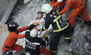 Rescue personnel help a child rescued at the site where a 17-storey apartment building collapsed during an earthquake in Tainan, southern Taiwan, February 6, 2016. Stringer/Reuters