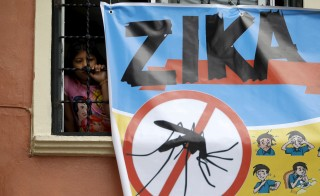 A woman looks on next to a banner as soldiers and municipal health workers take part in cleaning of the streets, gardens and homes as part of the city's efforts to prevent the spread of the Zika virus vector, the Aedes aegypti mosquito, in Tegucigalpa, Honduras. Photo by Jorge Cabrera/Reuters
