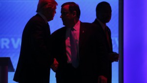 Republican U.S. presidential candidate businessman Donald Trump (L) whispers to Governor Chris Christie (C) as Dr Ben Carson (R) walks past during a commercial break at the Republican U.S. presidential candidates debate sponsored by ABC News at Saint Anselm College in Manchester, New Hampshire February 6, 2016.     REUTERS/Carlo Allegri - RTX25SPD