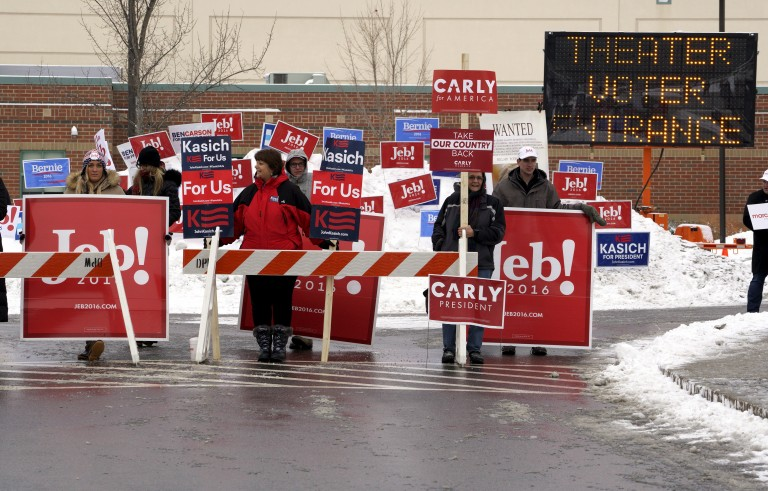 Supporters of U.S. presidential candidates stand at the entrance to the polling station for the presidential primary at Bedford High School in Bedford, New Hampshire February 9, 2016.   REUTERS/Rick Wilking - RTX266D5