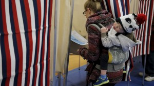 A woman with a child on her back prepares to mark her ballot in a voting booth on voting day in Bedford, New Hampshire, February 9, 2016. REUTERS/Carlo Allegri - RTX267M6