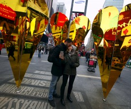 """(L-R) Caio Nader kisses his girlfriend Juliana Avilla, both from Rio de Janeiro, Brazil, at the """"Heart of Hearts"""" installation by Collective-LOK, which won the annual Times Square Valentine Heart Design competition, in Times Square, New York February 10, 2016. REUTERS/Andrew Kelly         EDITORIAL USE ONLY. NO RESALES. NO ARCHIVE - RTX26E91"""