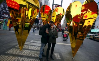 "(L-R) Caio Nader kisses his girlfriend Juliana Avilla, both from Rio de Janeiro, Brazil, at the ""Heart of Hearts"" installation by Collective-LOK, which won the annual Times Square Valentine Heart Design competition, in Times Square, New York February 10, 2016. REUTERS/Andrew Kelly         EDITORIAL USE ONLY. NO RESALES. NO ARCHIVE - RTX26E91"