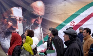 People walk past a large picture of the late leader of the Islamic Revolution Ayatollah Ruhollah Khomeini (R) and Iran's Supreme Leader Ayatollah Ali Khamenei, during a ceremony marking the 37th anniversary of the Islamic Revolution, in Tehran February 11, 2016. REUTERS/Raheb Homavandi/TIMA  ATTENTION EDITORS - THIS IMAGE WAS PROVIDED BY A THIRD PARTY. FOR EDITORIAL USE ONLY.  - RTX26GZ6