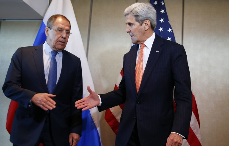 Secretary of State John Kerry (right) and Russian Foreign Minister Sergei Lavrov go for a handshake before their bilateral talks in Munich, Germany, on Feb. 11, ahead of the International Syria Support Group meeting. Photo by Michael Dalder/Reuters