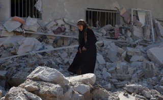 A woman makes her way through the rubble of damaged buildings after airstrikes by pro-Syrian government forces in the rebel held town of Dael, in Deraa Governorate, Syria February 12, 2016. REUTERS/Alaa Al-Faqir - RTX26N2E