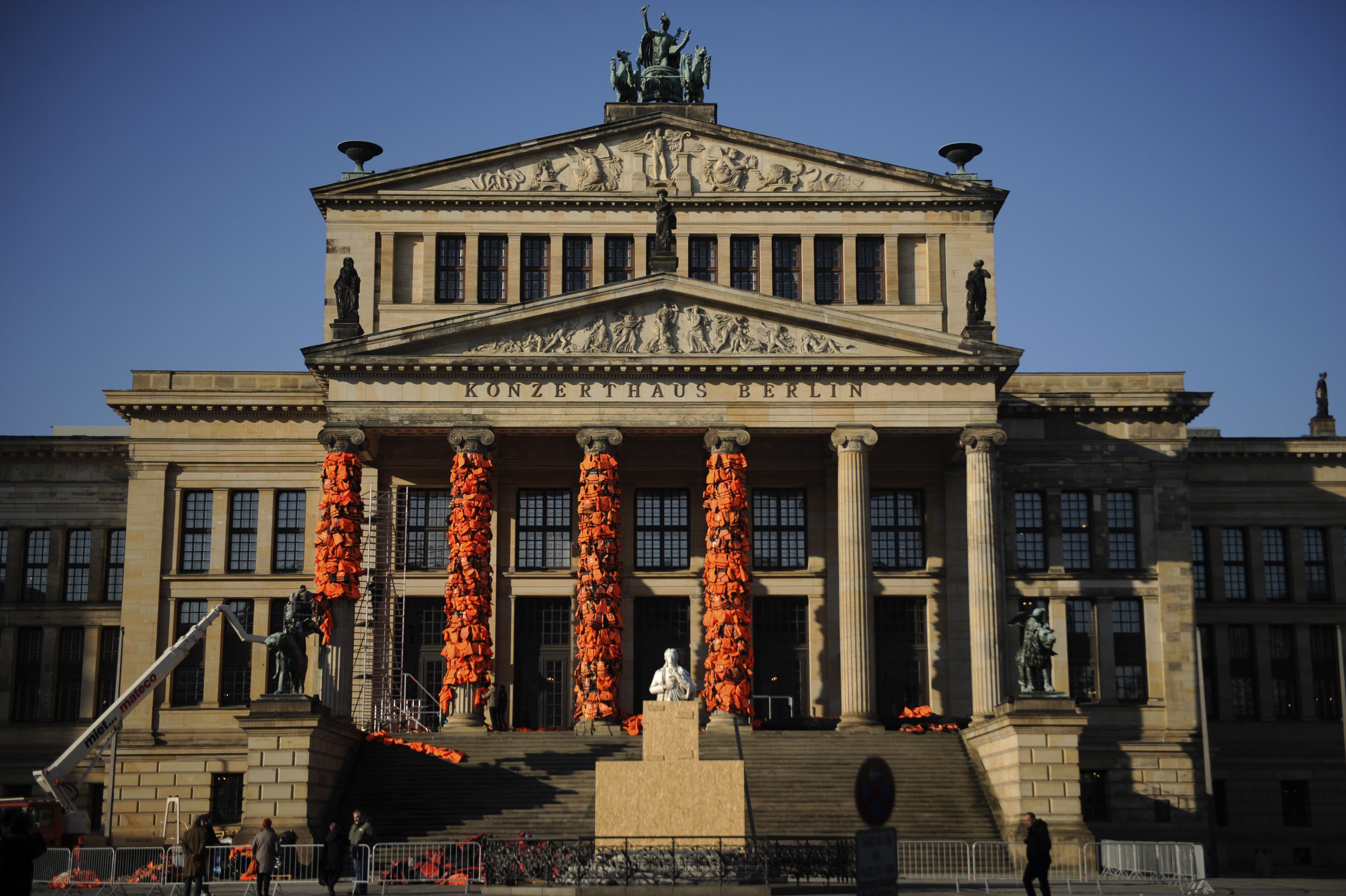 Workers bulid up an instalation by Chinese artist and free-speech advocate Ai Weiwei with life jackets left by migrants on Greek beaches on columns at the Schauspielhaus concert hall during the 66th Berlinale International Film Festival in Berlin, Germany February 13, 2016. Ai Weiwei used about 14,000 discarded life jackets, which he obtained from authorities from the Greek island of Lesbos for this memorial project.  REUTERS/Stefanie Loos FOR EDITORIAL USE ONLY. NOT FOR SALE FOR MARKETING OR ADVERTISING CAMPAIGNS.   - RTX26QMV