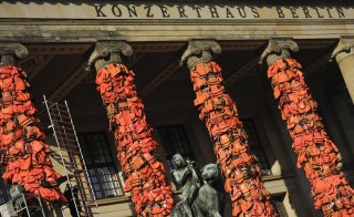 Workers bulid up an instalation by Chinese artist and free-speech advocate Ai Weiwei with life jackets left by migrants on Greek beaches on columns at the Schauspielhaus concert hall during the 66th Berlinale International Film Festival in Berlin, Germany February 13, 2016. Ai Weiwei used about 14,000 discarded life jackets, which he obtained from authorities from the Greek island of Lesbos for this memorial project.  REUTERS/Stefanie Loos FOR EDITORIAL USE ONLY. NOT FOR SALE FOR MARKETING OR ADVERTISING CAMPAIGNS.   - RTX26QN1