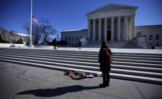 Flowers are seen as a woman stands in front of the Supreme Court building in Washington D.C. after the death of U.S. Supreme Court Justice Antonin Scalia, February 14, 2016. REUTERS/Carlos Barria - RTX26VSV