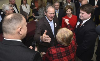Former President George W. Bush hugs a woman with former first lady Laura Bush at his side as they campaign for the first time in the 2016 campaign in support of his brother, Republican presidential candidate Jeb Bush, in Columbia, South Carolina. Photo by Rainier Ehrhardt/Reuters