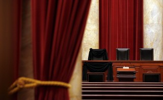 The bench of late Supreme Court Justice Antonin Scalia is seen draped with black wool crepe in memoriam inside the Supreme Court in Washington February 16, 2016. Photo by Carlos Barria/Reuters