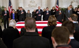 Supreme Court Justices make the sign of the cross during prayers at a private ceremony in the Great Hall of the Supreme Court where late Supreme Court Justice Antonin Scalia lies in repose in Washington February 19, 2016. From back left are Counselor to the Chief Justice Jeffrey Minear, and Supreme Court Justices Elena Kagan, Samuel Anthony Alito, Jr., Ruth Bader Ginsburg, Anthony M. Kennedy, Chief Justice John G. Roberts, Jr., Clarence Thomas, Stephen G. Breyer, and Sonia Sotomayor. REUTERS/Jacquelyn Martin/POOL - RTX27QG8