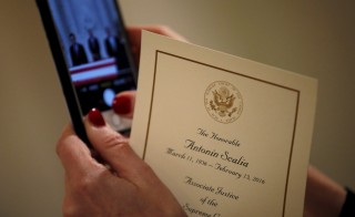 A woman takes a picture of the casket containing the remains of the late U.S. Supreme Court Justice Antonin Scalia as it lies in repose in the Great Hall of the Supreme Court in Washington February 19, 2016. Scalia died on February 13, 2016 at the age of 79. REUTERS/Carlos Barria - RTX27R1P