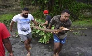 Fijian men clear a road of a fallen tree in Fiji's capital Suva after Cyclone Winston swept across Viti Levu Island, February 21, 2016. Fijian officials were assessing the damage on Sunday after one of the most powerful storms recorded in the southern hemisphere tore through the archipelago, with early reports of widespread disruption and at least six people confirmed dead. Taniela Qalilawa/Reuters