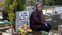 The mother of Suleyman Uslu sits next to the grave of her son, a People's Protection Units (YPG) member who was killed during fighting against Islamic State in north Syria, at a cemetery in Diyarbakir Turkey February 25, 2016. REUTERS/Sertac Kayar  - RTX28MBM