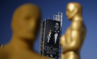 An Oscar statue overlooks a Chris Rock poster at the entrance to the Dolby Theatre as preparations continue for the 88th Academy Awards in Hollywood, Los Angeles, California February 25, 2016. Photo by Lucy Nicholson/Reuters.