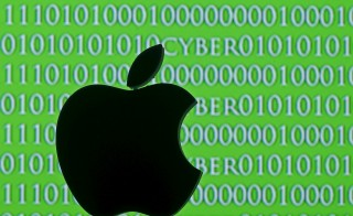 3D printed Apple logo are seen in front of a displayed cyber code in this photo illustration. Photo illustration by Dado Ruvic/Reuters