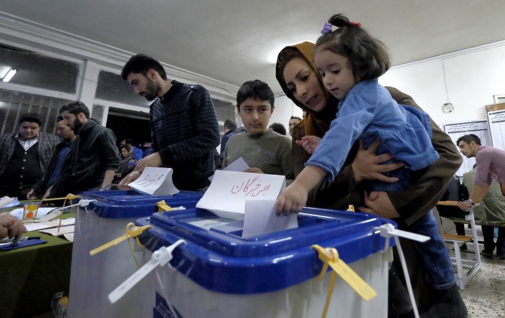 An Iranian woman holding her daughter casts her ballot during elections for the parliament and Assembly of Experts, which has the power to appoint and dismiss the supreme leader, in Tehran February 26, 2016.Raheb Homavandi/Reuters