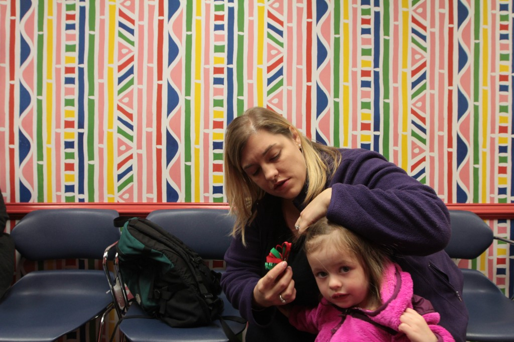 Lauren Shillinger replaces a hairbow for her daughter, Brynleigh, 2, before their two-year check-up with their pediatrician. They plan to discuss Brynleigh's vaccine schedule, and how to administer them in a way that won't prompt fevers and possible seizures. Photo by Joshua Barajas