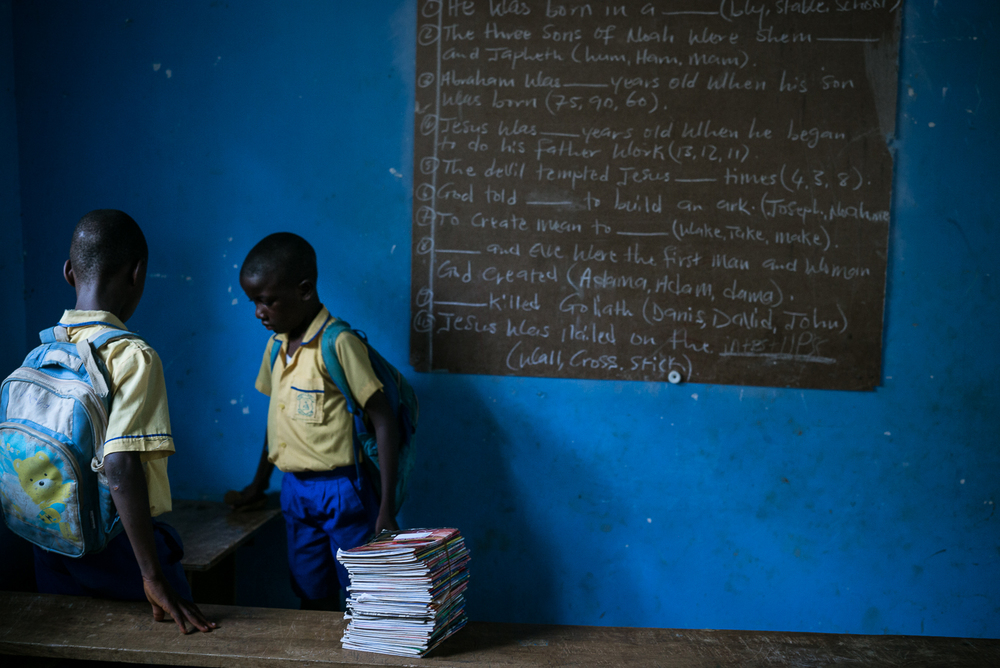 Two students hand out composition books for an exam at the We Yone school in George Brook, Freetown, Sierra Leone. Photo by Sara May