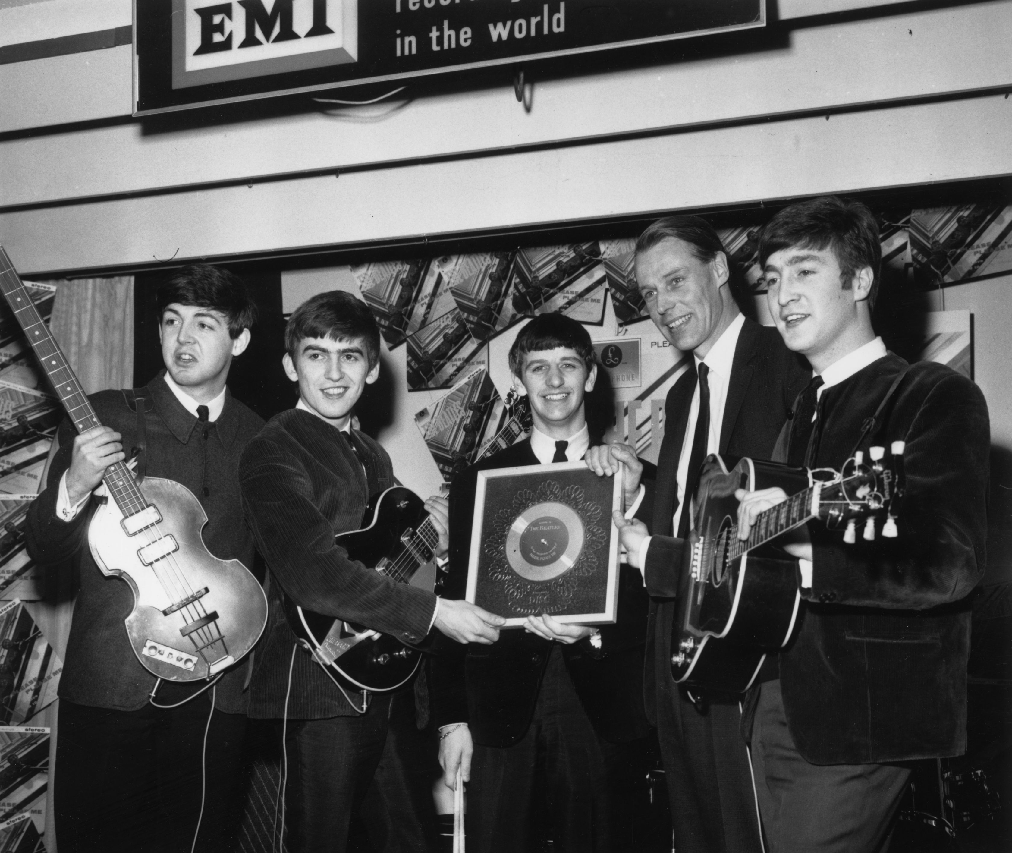 The Beatles hold their silver disc in 1963. Left to right are: Paul McCartney, George Harrison, Ringo Starr, producer George Martin of EMI and John Lennon. Photo by Chris Ware/Keystone/Getty Images