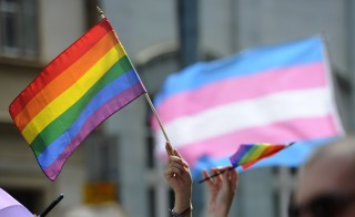 People hold up rainbow flags during an lesbian, gay, bisexual and transgender (LGBT) parade. Photo by Samuel Kubani/AFP/Getty Images