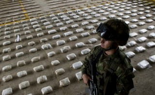 "A Colombian Army soldier stands next to packages of seized cocaine during a press conference at a Military Base in Bahia Solano, department of Choco, Colombia, on March 14, 2015. A joint operation between Colombia's Army and Air Force, intercepted a boat near the municipality of Nuqui, west of the country, with 583 kilos of cocaine which, according to authorities, belonged to the criminal gang ""Clan Usuga"" and was going to be sent to Central America. AFP PHOTO / LUIS ROBAYO        (Photo credit should read LUIS ROBAYO/AFP/Getty Images)"