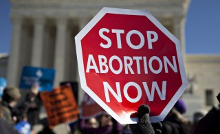 A demonstrator holds up a sign in support of pro-life rights outside the U.S. Supreme Court in Washington, D.C., U.S., on Wednesday, March 2, 2016. Supreme Court justices clashed in their first abortion showdown in almost a decade as a pivotal justice suggested the court could stop short of a definitive ruling on a disputed Texas law regulating clinics. Photo by Andrew Harrer/Bloomberg via Getty Images
